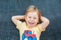 一个小白肤金发的孩子男孩的顶视图有空间文本的和标志的在老木背景 混乱的,突发的灵感概念 免版税图库摄影