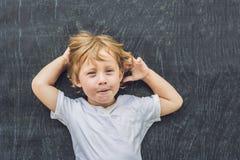 一个小白肤金发的孩子男孩的顶视图有空间文本的和标志的在老木背景 混乱的,突发的灵感概念 免版税库存照片