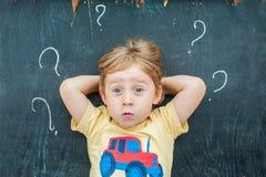 一个小白肤金发的孩子男孩的顶视图有问号的在黑板 混乱、激发灵感和选择的概念 免版税库存图片
