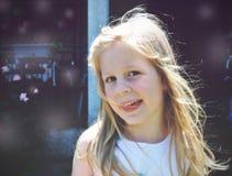 一个小白肤金发的微笑的女孩的画象;软的减速火箭的样式 库存照片
