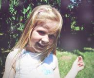 一个小白肤金发的微笑的女孩的画象;软的减速火箭的样式 免版税库存照片