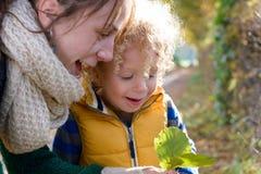 一个小白肤金发的男孩和他的妈妈使用外面 库存照片