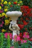 一个小的天使的雕象在一个热带庭院里 库存照片