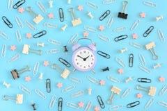 一个小的淡紫色闹钟,在办公用品凌乱的中心  白色和黑纸夹,职员 免版税库存图片