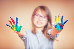 一个小的青春期前的学生女孩陈列的画象绘了手 被定调子的照片 图库摄影