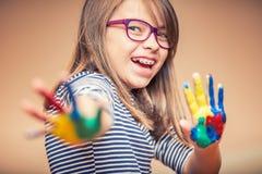 一个小的青春期前的学生女孩陈列的画象绘了手 被定调子的照片 免版税库存图片