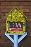 以一个小的黄色摊的形式街道图书馆有自由书的 箱子使用作为图书馆交换 免版税库存照片