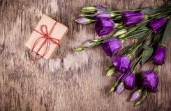 一个小礼物盒和花在老木背景 库存图片