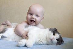 一个小笑的孩子拥抱一只大蓬松猫 免版税库存照片