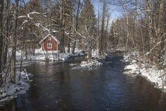 一个小红色房子位于河 库存图片