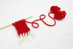 一个小红色毛线球和红色圣诞老人围巾起点在白色钩针编织背景的 浪漫圣诞节概念 编织的w 库存图片