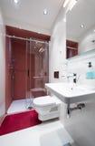 一个小红色白色卫生间的内部 免版税库存照片