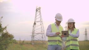 一个小组一个高压能源厂的工程师有片剂的和图画走并且谈论供应的一个计划  股票录像