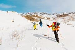 一个小组三freeriders攀登backcountry滑雪的山沿狂放的倾斜  库存图片