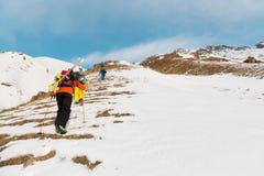 一个小组三freeriders攀登backcountry滑雪的山沿狂放的倾斜  免版税库存照片