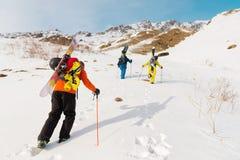 一个小组三freeriders攀登backcountry滑雪的山沿狂放的倾斜  免版税图库摄影