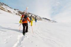 一个小组三freeriders攀登backcountry滑雪的山沿狂放的倾斜  库存照片