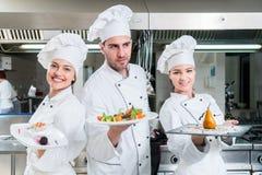 一个小组与一顿膳食的年轻厨师posig在豪华餐馆 免版税库存图片