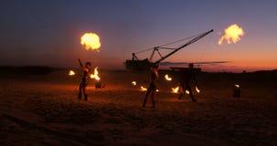 一个小组人和妇女火展示在沙子的晚上以火和塔吊为背景 股票录像