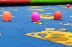 一个小组几个色的球在游戏室的地板上驱散了 库存照片