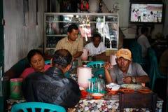 一个小组印度尼西亚朋友吃在一间地方小餐馆 免版税库存照片
