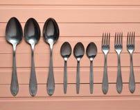 一个小组叉子,在橙色木桌上的匙子 刀叉餐具 顶视图 免版税库存照片