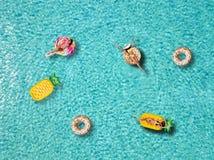 一个小组可爱的妇女享用在形状的浮游物的太阳 库存图片