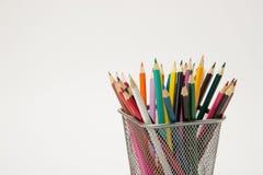 一个小组在一块文字玻璃的色的铅笔在一白色backgro 免版税库存照片