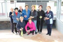 一个小组在使用以后的愉快的资深妇女滚保龄球 库存图片