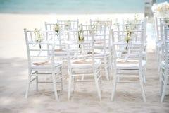 一个小组在沙子的白色chiavari椅子海滩婚礼准备的,玫瑰花瓣-后部视图锥体  免版税库存照片