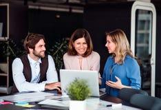 一个小组坐在办公室的商人,使用膝上型计算机 图库摄影