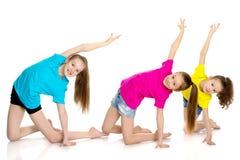 一个小组女孩体操运动员执行锻炼 免版税库存照片