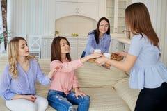 一个小组女孩的朋友谈话在一次会议上在屋子里 免版税库存照片