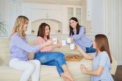 一个小组女孩的朋友谈话在一次会议上在屋子里 图库摄影