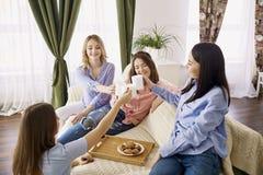 一个小组女孩的朋友谈话在一次会议上在屋子里 免版税库存图片