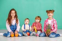 一个小组孩子在屋子里坐 有用的果子 骗局 库存照片