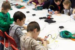 一个小组孩子学会在同水准帮助下画3D笔 免版税库存照片