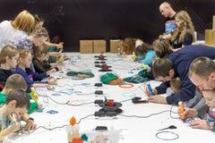 一个小组孩子学会在同水准帮助下画3D笔 库存照片