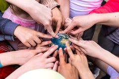 一个小组孩子拿着地球的小玩具地球 免版税库存照片