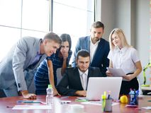 一个小组审查在膝上型计算机的办公室工作者想法 免版税库存图片