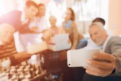 一个小组年轻和老人在老人院在有一名年长妇女的一个智能手机做一selfie 库存照片