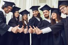 一个小组年轻毕业生提高了他们的赞许 库存图片
