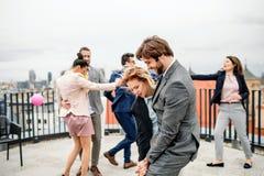 一个小组快乐的买卖人有屋顶大阳台的党户外在城市,跳舞 免版税库存图片