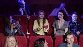 一个小组快乐的年轻朋友投掷玉米花在戏院 股票录像