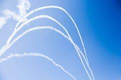 一个小组战斗机军用飞机的专业飞行员在一个晴朗的晴天在蓝天显示把戏,离开beauti 库存照片