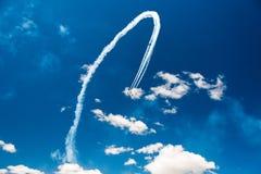 一个小组战斗机军用飞机的专业飞行员在一个晴朗的晴天在蓝天显示把戏,离开beauti 免版税图库摄影