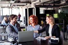 一个小组有坐在办公室的膝上型计算机的年轻商人,谈话 图库摄影