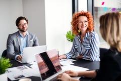 一个小组有坐在办公室的膝上型计算机的年轻商人,谈话 免版税库存照片
