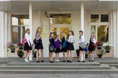 一个小组有背包的女小学生上学 免版税库存照片