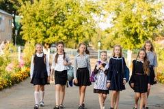 一个小组有背包的女小学生上学 免版税库存图片